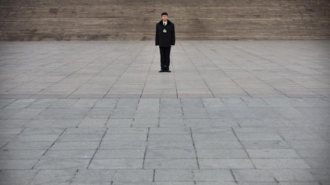 A security person stands guard in front of the Great Hall of the People before the opening session of the annual National People's Congress in Beijing, Thursday, March 5, 2015. China announced a lower economic growth target for this year and promised to open more industries to foreign investors as it tries to make its slowing, state-dominated economy more productive. (AP Photo/Mark Schiefelbein)