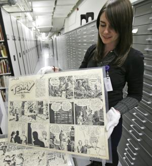 "In this Wednesday, Oct. 23, 2013 photo, Caitlin McGurk holds up a cartoon titled ""Terry and the Pirates"" by Milton Caniff at the Billy Ireland Cartoon Library & Museum in Columbus, Ohio. The whole thing started with Caniff, the influential comic artist whose beloved ""Terry and the Pirates"" and ""Steve Canyon"" adventure strips lived in the nation's funny papers for a half century. Caniff graduated from Ohio State University and loved the place so much he wanted his original art and other papers to be kept here forever. (AP Photo/Tony Dejak)"