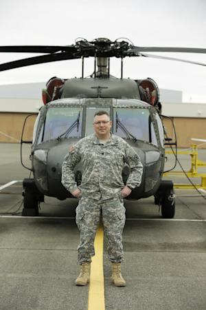 """Lt. Col. Clayton Braun, of the Washington State Army National Guard, poses for a photo, Wednesday, Jan. 20, 2016, at Joint Base Lewis-McChord in Washington state in front of a military helicopter that could be used in response to a major earthquake. Since 2013, Braun has led a team putting together a military response plan should an earthquake and tsunami happen in Washington state, as part of federal, state and military preparation for the """"Big One"""" along the Cascadia Subduction Zone. (AP Photo/Ted S. Warren)"""