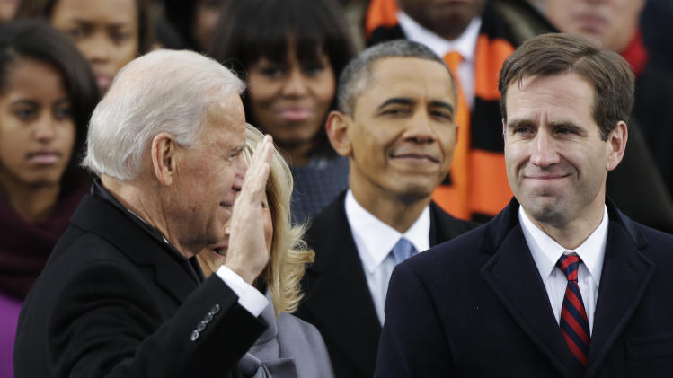 President Barack Obama, center and Beau Biden, Attorney of Deleware, right, watch as his father Joe Biden is sworn in at the ceremonial swearing-in at the U.S. Capitol during the 57th Presidential Inauguration in Washington, Monday, Jan. 21, 2013. (AP Photo/Pablo Martinez Monsivais)