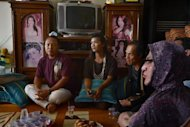 In this photograph taken on January 29, 2013, a group of Indonesian transgenders listen to Yulianus Rettoblaut, a prominent activist, at her house in the suburbs of Jakarta that she opened to transgenders last year. About a dozen elderly Indonesians live out their twilight years there, in what is possibly the world's first old folks' home for transgenders
