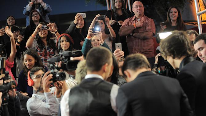 """Fans take pictures as One Direction arrives at the """"The X Factor"""" season finale results show at CBS Television City on Thursday, Dec. 20, 2012, in Los Angeles. (Photo by Jordan Strauss/Invision/AP)"""