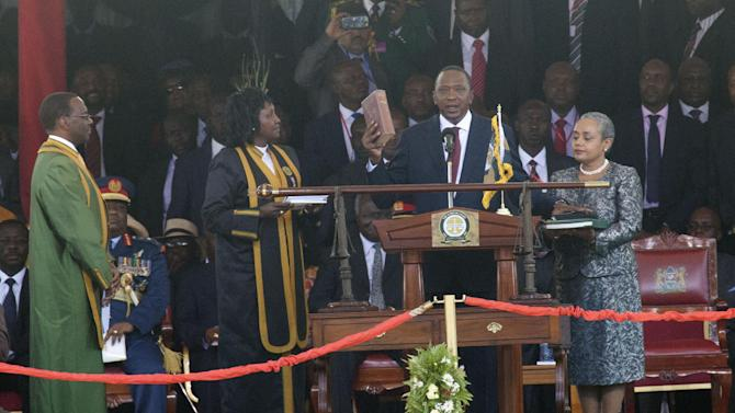 President elect Uhuru Kenyatta holds the bible in his right hand as he take oath of office as the fourth president of the Republic of Kenya at Moi International Sports Complex in Nairobi, Kenya Tuesday, April 9, 2013, watched by his wife Margaret Uhuru, right and the Supreme court judge, Willy Mutunga, left and  Chief Registrar of the Supreme court Glady Sholey.Uhuru Kenyatta was sworn in as the Kenya's fourth president Tuesday in a stadium filled with tens of thousands of Kenyans and a dozen African leaders. Kenyatta, 51, the son of Kenya's first president, becomes the second sitting African president to face charges at the International Criminal Court over allegations he helped orchestrate the vicious tribe-on-tribe violence that marred Kenya's 2007 presidential election. A jubilant crowd swathed in Kenyatta's campaign color of red loudly interrupted the swearing-in with rapturous cheers. (AP Photo/Sayuyid Azim)