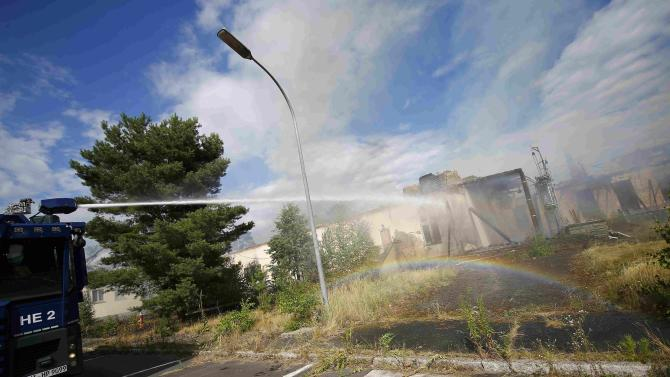 Police use a water cannon to help firefighters to extinguish a fire which broke out at a former U.S. airfield in Erlensee