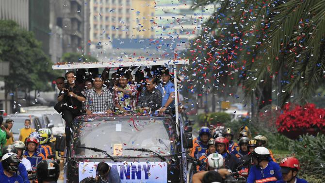 """WBO welterweight champion Manny """"Pacman"""" Pacquiao gestures as the confetti showers on his convoy during a victory parade in Manila"""