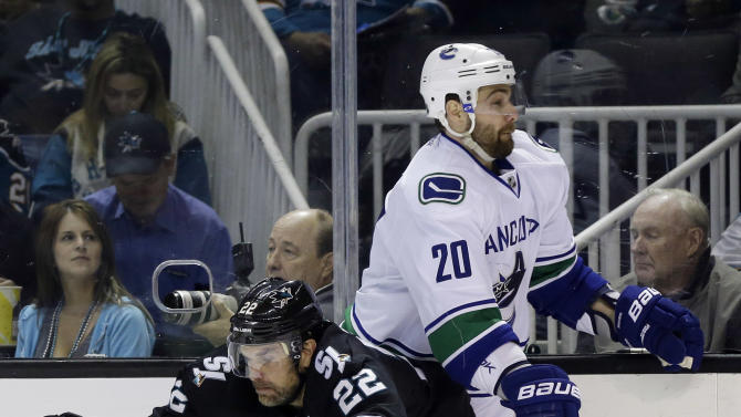 San Jose Sharks defenseman Dan Boyle (22) collides with Vancouver Canucks left wing Chris Higgins (20) during the second period of Game 4 of their first-round NHL hockey Stanley Cup playoff series in San Jose, Calif., Tuesday, May 7, 2013. (AP Photo/Marcio Jose Sanchez)