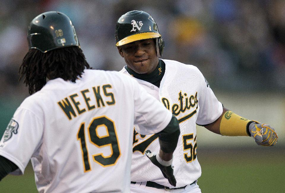 Oakland Athletics' Yoenis Cespedes, right, celebrates with teammate Jemile Weeks (19) after hitting a two-run home run off New York Yankees' Freddy Garcia in the first inning of a baseball game on Thursday, July 19, 2012, in Oakland, Calif. (AP Photo/Ben Margot)