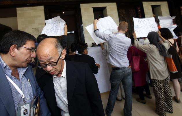 Delegates take a detour as activists protest outside the plenary room of the ninth World Trade Organization Ministerial Conference in Nusa Dua