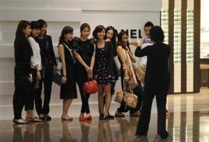 File picture shows shoppers posing in front of a Chanel luxury boutique in Shanghai
