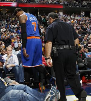 New York Knicks forward Carmelo Anthony walks off the court with a police escort in the third quarter of the Denver Nuggets' 117-94 victory over the Knicks in an NBA basketball game in Denver on Wednesday, March 13, 2013. Anthony left the game, which was his first in Denver since he was traded in 2011, because of sore knes. (AP Photo/David Zalubowski)