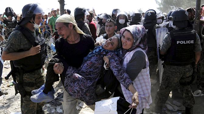 Migrants rush to cross into Macedonia after Macedonian police allowed a small group of people to pass through a passageway, as they try to regulate the flow of migrants at the Macedonian-Greek border