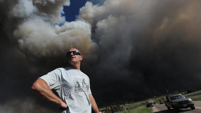 Dave Dunlap watches from the bed of his truck as a wildfire crosses Black Forest Road near his home Tuesday afternoon, June 11, 2013, in Colorado Springs, Colo. The Black Forest Fire was one of at least three significant wildfires burning in Colorado amid gusty winds and record-breaking hot, dry weather. (AP Photo/The Colorado Springs Gazette, Christian Murdock) MAGS OUT