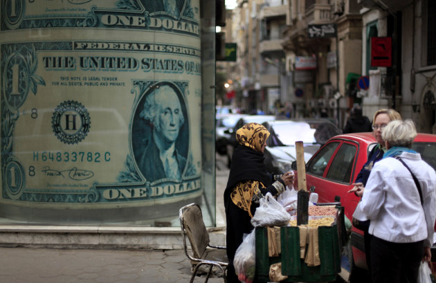 An Egyptian vendor sells nuts in front of a giant poster of a U.S. dollar outside a currency exchange office in Cairo, Egypt, Tuesday, Dec. 25, 2012. As Egypt prepared to release official results from
