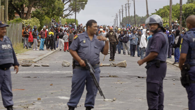South African Policeman provide security as farm workers demonstrate against low wages in the background, by placing rocks in a road, in the town of Grabouw, South Africa, Wednesday, Jan. 9, 2013. Striking farm workers on Wednesday set up barricades and threw stones at motorists and police in a South African province whose vineyards are vital to the wine industry, prompting riot officers to close roads and arrest at least 50 demonstrators, South African media reported. (AP Photo/Schalk van Zuydam)