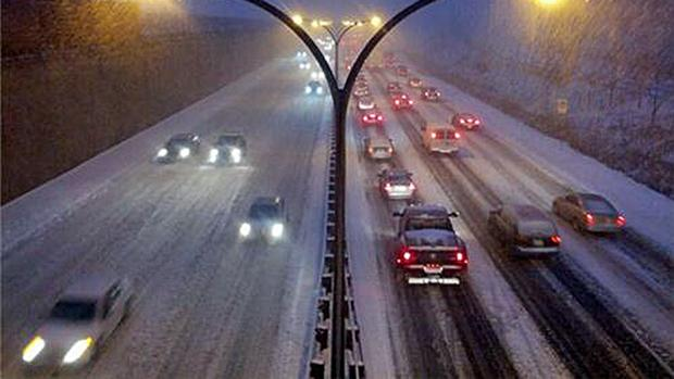 Drivers crawl along a snow-covered Gardiner Expressway on Friday morning. Snow is forecast to fall throughout the day.