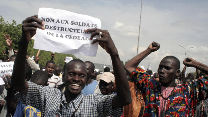 "FILE - In this Oct.18, 2012 file photo, a man carries a sign reading ""No to the destructive soldiers of ECOWAS"" as Malians opposed to a military intervention to retake Mali's Islamist-controlled north march in the streets of the capital, Bamako, Mali. France is moving surveillance drones to western Africa amid rising concerns that an al-Qaida offshoot and its allies who control northeast Mali represent a major threat to French interests abroad and possibly at home. With six French hostages held by Islamic militants in the region, France is facing a delicate task, but has garnered support from other Western powers including the United States to keep Mali from becoming a new launchpad for global terrorism. (AP Photo/Harouna Traore, File)"