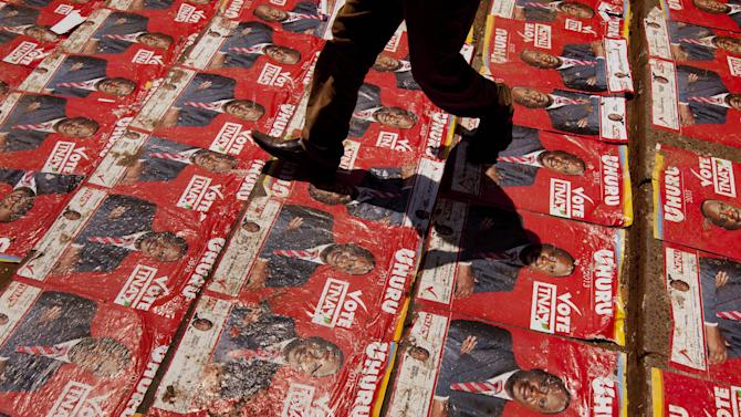 A supporter walks down steps plastered with campaign posters of Kenyan Presidential candidate Uhuru Kenyatta at his campaign's final rally at Uhuru Park in Nairobi, Kenya Saturday, March 2, 2013. Kenya's top two presidential candidates - Uhuru Kenyatta and Raila Odinga - held their final rallies Saturday before large and raucous crowds ahead of Monday's vote, which is the first nationwide election since Kenya's December 2007 vote descended into tribe-on-tribe violence that killed more than 1,000 people. (AP Photo/Ben Curtis)