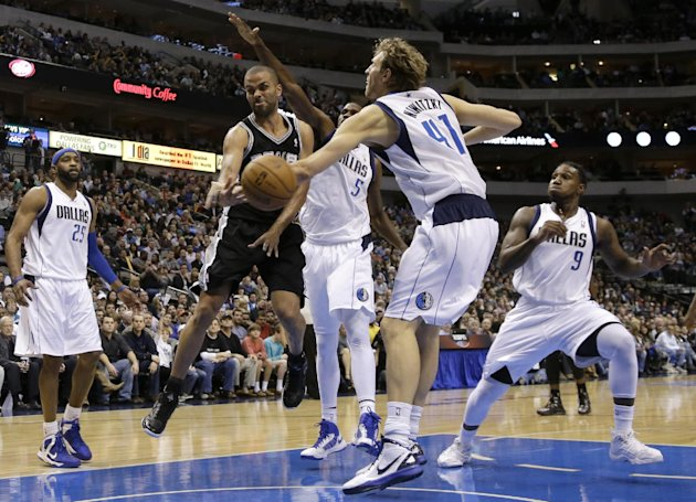 San Antonio Spurs' Tony Parker, second from left, of France, passes the ball from beneath the basket as Dallas Mavericks' Dirk Nowitzki (41), of Germany, defends in the second half of an NBA basketbal
