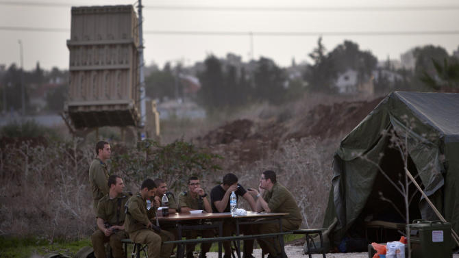 Israeli soldiers sit next to Iron Dome defense system launch site, deployed in Tel Aviv to intercept incoming missiles from Gaza, Saturday, Nov. 17, 2012. Israel bombarded the Hamas-ruled Gaza Strip with nearly 200 airstrikes early Saturday, the military said, widening a blistering assault on Gaza rocket operations to include the prime minister's headquarters, a police compound and a vast network of smuggling tunnels. (AP Photo/Oded Balilty)