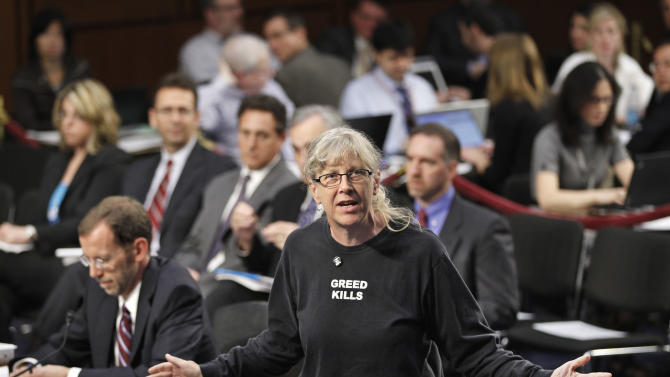 """Wearing a shirt that says """"Greed Kills,"""" a protester disrupts a hearing of the deficit supercommittee with Congressional Budget Office (CBO) Director Douglas Elmendorf, seated at left, Wednesday, Oct. 26, 2011, on Capitol Hill in Washington.   (AP Photo/J. Scott Applewhite)"""