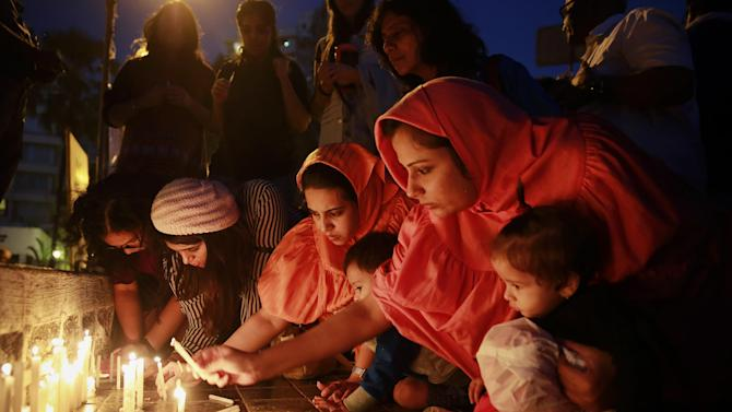 Indians lights candles during a prayer meeting in memory of the victims of Tuesday's Taliban attack in Peshawar, in Mumbai, India,Thursday, Dec. 18, 2014. The Pakistani government and military vowed a stepped up campaign aimed at rooting out militant strongholds in the country's tribal regions along the border with Afghanistan after a Taliban massacre that killed more than 140 people, mostly children, on a military-run school. (AP Photo/Rafiq Maqbool)