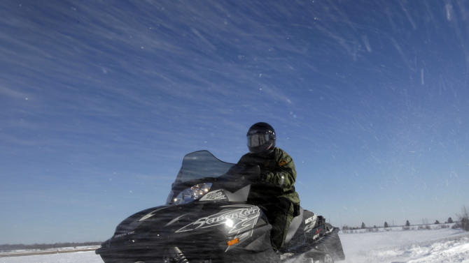 In this Feb. 10, 2011 photo, snow flies over U.S. Border Patrol agent Glenn Pickering as he rides a snowmobile along the St. Lawrence River in Massena, N.Y. This is the United States' forgotten border, where federal agents and police play cat-and-mouse with smugglers and illegal immigrants along 4,000 miles of a mostly unmarked and unfortified frontier with Canada.(AP Photo/Mike Groll)