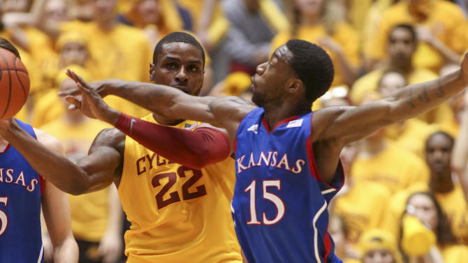 Kansas guard Elijah Johnson tries to knock the ball away from Iowa State forward Anthony Booker (22) during the first half of an NCAA college basketball game Monday, Feb. 25, 2013, at Hilton Coliseum in Ames, Iowa. Johnson scored 39 points and Kansas won the game 108-96 in overtime. (AP Photo/Justin Hayworth)