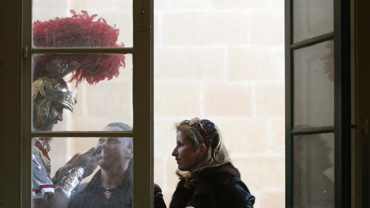 A participant dressed as a Roman soldier looks at a photo on a phone with two friends on a balcony of a parish centre next to the Rotunda of Mosta, in preparation for a Good Friday procession in Mosta