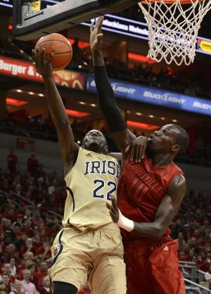 Notre Dame's Jerian Grant, left, attempts a shot over the defense of Louisville's Gorgui Dieng during the first half of an NCAA college basketball game on Saturday March 9, 2013, in Louisville, Ky. (AP Photo/Timothy D. Easley)