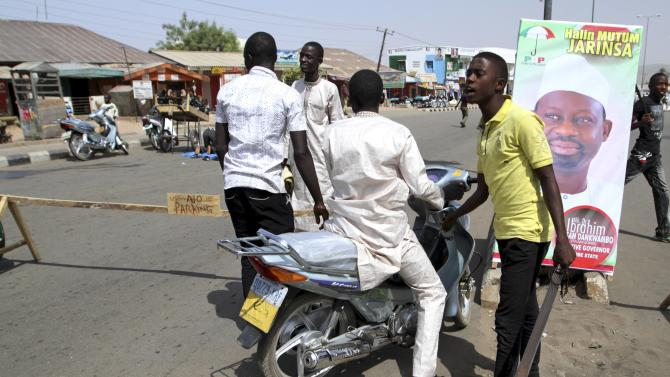 A youth volunteer holds a machete at a checkpoint near Specialist Hospital Gombe