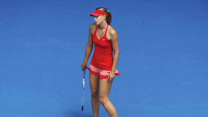 Sharapova of Russia reacts after missing a return to Peng of China during their women's singles match at the Australian Open 2015 tennis tournament in Melbourne