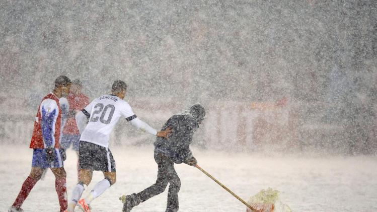 United States defender Geoff Cameron (20) helps a grounds keeper shovel snow off the field during the second half of a World Cup qualifier soccer match against Costa Rica in Commerce City, Colo., Friday, March 22, 2013. The United States beat Costa Rica 1-0. (AP Photo/Jack Dempsey)