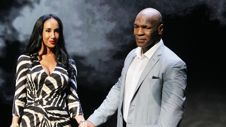 "This image released by Starpix shows, former boxer Mike Tyson, right, holds hands with his wife Kiki Tyson at the curtain call for the opening night of ""Mike Tyson: Undisputed Truth,"" Thursday, Aug. 2, 2012 at the Longacre Theatre in New York.  The one man show starring Tyson was directed by Spike Lee, and written by Kiki Tyson. (AP Photo/Starpix, Amanda Schwab)"