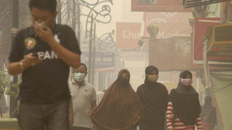 People wear masks to protect themselves from the haze in Pekanbaru, Riau province, Indonesia, Thursday, March 13, 2014. Heavy smoke from illegal fires set to clear land for plantations has blanketed parts of Indonesia's Sumatra island, disrupting flights and hampering search efforts for the missing Malaysia Airlines jetliner, officials and a pilot said Thursday. (AP Photo/Rony Muharrman)