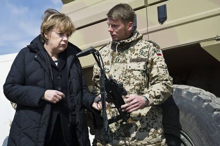 File photo of German Chancellor Merkel looking at Heckler & Koch MP7 submachine gun during a visit to the German army's Camp Marmal in Mazar-e-Sharif