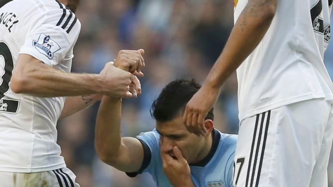 Manchester City's Sergio Aguero holds his face following a tackle during their English Premier League soccer match against Swansea City at the Etihad stadium in Manchester
