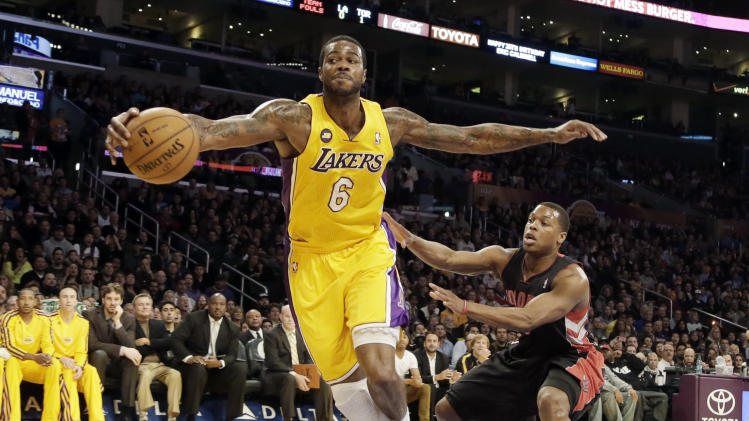 Los Angeles Lakers forward Earl Clark (6) saves a ball heading out of bounds as Toronto Raptors' Kyle Lowry defends during the first half of an NBA basketball game in Los Angeles Friday, March 8, 2013. (AP Photo/Reed Saxon)