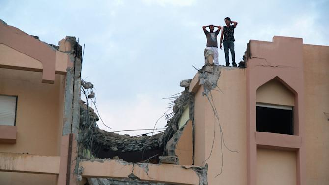 Two men stand on the roof of a damaged building after a Libyan war plane crashed in Tobruk