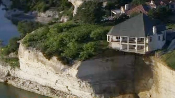 In this image taken from Tuesday, June 10, 2014 video provided by WFAA-TV, a luxury house teeters on a cliff about 75 feet above Lake Whitney in Whitney, Texas. WFAA-TV reported Wednesday, June 11, 2014 that the house has been condemned and the owners evacuated about two weeks ago. (AP Photo/WFAA.com)