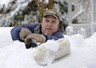 Hank Luth brushes snow piled high on his car parked in his driveway on Terry Ct. after a snow storm on Saturday, Feb. 9, 2013 in Glen Head, N.Y. (AP Photo/Kathy Kmonicek)