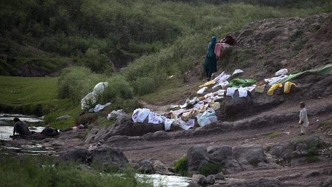 Pakistani displaced women wash their laundry in a polluted canal in suburbs of Islamabad, Pakistan, Friday, May 29, 2015.  (AP Photo/B.K. Bangash)