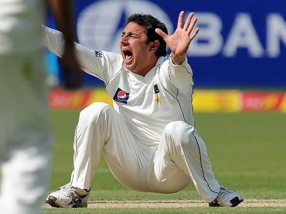 Pakistan's spinner Saeed Ajmal celebrates after he dismissed England's cricketer Eoin Morgan (unseen) during the first day of the opening Test match between Pakistan and England at the Dubai I