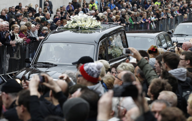 FILE- The hearse bearing the coffin of Sir Jimmy Savile moves slowly as crowds of fans look on, in Leeds, England, in this file photo dated Wednesday Nov. 9, 2011. The TV personality and broadcaster widely known for his charitable works is being revealed by police as a sexual predator. Relevations about Savile as a sex offender have shaken the British public and questions are being asked in the media about whether the society that gave him fame and fortune, also helped keep his crimes from coming out. (AP Photo/Jon Super, file)