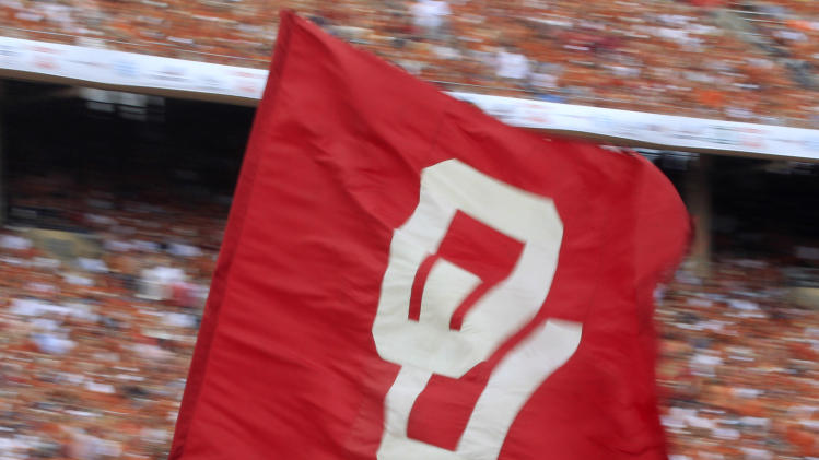 An Oklahoma flag is carried across the field after a touchdown was scored during the first half of an NCAA college football game against the Texas at the Cotton Bowl Saturday, Oct. 13, 2012, in Dallas. (AP Photo/LM Otero)