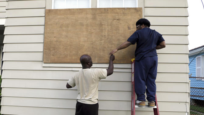 Stacey Davis, left, hands a screw to his son as they board up windows on their home before Tropical Storm Isaac hits Tuesday, Aug. 28, 2012, in New Orleans. Tropical Storm Isaac is churning it's way across the Gulf of Mexico towards New Orleans. (AP Photo/David J. Phillip)