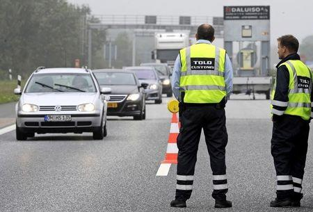 Danish customs officers watch traffic at a checkpoint on the German-Danish border crossing in Froslev