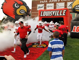 Bobby Petrino runs on to the field with his team. (AP)
