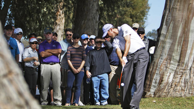 Matt Kuchar hits from the trees along the 13th fairway in the second round of the Northern Trust Open golf tournament at Riviera Country Club in the Pacific Palisades area of Los Angeles, Friday, Feb. 15, 2013. (AP Photo/Reed Saxon)