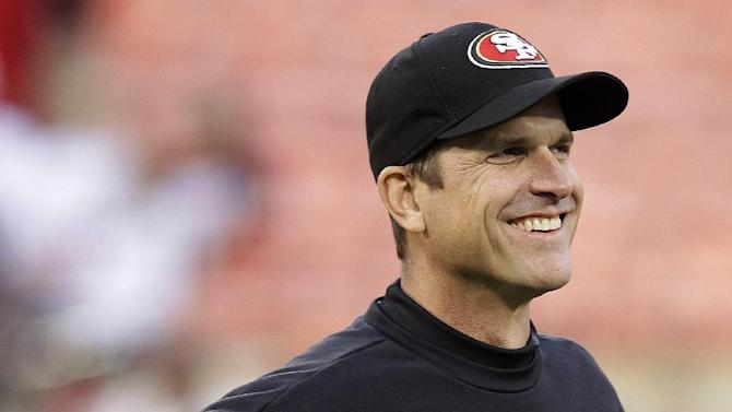 San Francisco 49ers head coach Jim Harbaugh smiles as he watches his team warm up before an NFL football game against the Chicago Bears in San Francisco, Monday, Nov. 19, 2012. Harbaugh underwent a minor procedure for an irregular heartbeat Thursday, Nov. 15. (AP Photo/Tony Avelar)