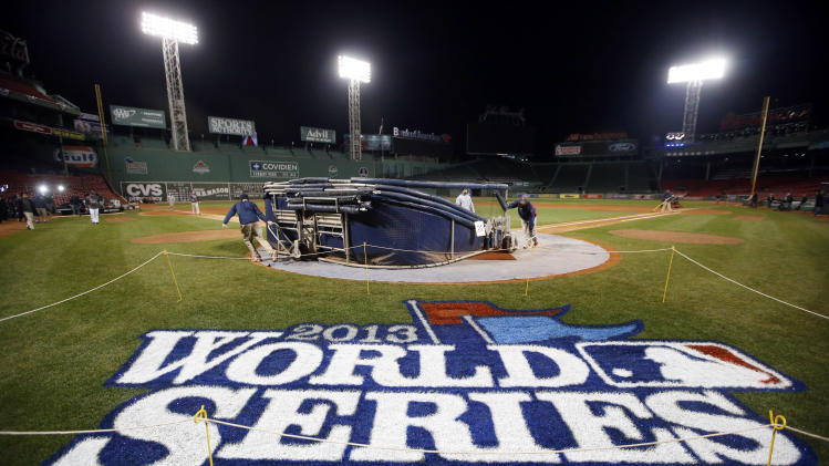 Grounds crew members dismantle the batting cage after the Boston Red Sox's workout at Fenway Park in Boston, Tuesday, Oct. 29, 2013. The Red Sox host the St. Louis Cardinals in Game 6 of baseball's World Series on Wednesday. (AP Photo/Elise Amendola)